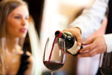 Fototapety Waiter pouring red wine to a woman
