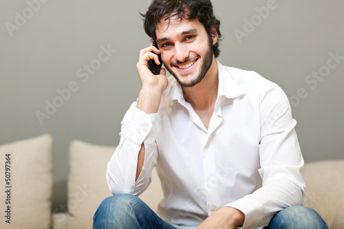 Relaxed young guy enjoying conversation on the sofa