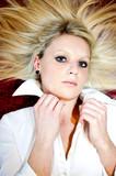 Attraktive blonde Frau liegt mit zerzausten Haaren am Boden