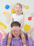 Father and daughter having fun in playroom
