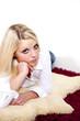 Junge attraktive Frau liegt auf Schaffell