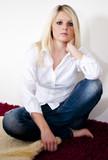Attraktive blonde Frau sitzt auf einem Teppich
