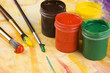 Paints and brushes againts painted multicolored background