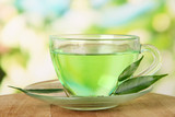 Transparent cup of green tea, on nature background