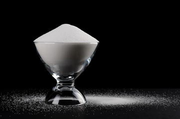 Pouring salt with glass cup isolated black background