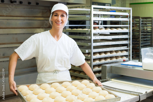 Female baker baking bread rolls