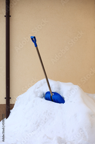 blue snow shovel standing up in deep snow