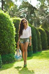 pretty woman in walking in garden park enjoying the flowers