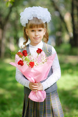 First grader girl posing with bouquet of autumn leaves
