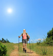 Young woman with backpack and hiking poles walking at sunny day