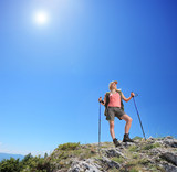 Young female with hiking poles posing at sunny day in mountain