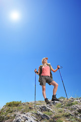 A young female with backpack and hiking poles posing at sunny da