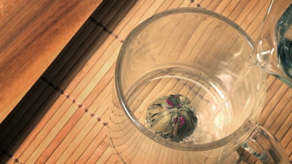 Green Chinese flower tea is brewed and dissolved in the glass