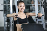 The girl is engaged in gym doing exercise strengthens chest poster