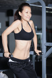 Woman at gym doing exercises to strengthen abdominal muscles poster