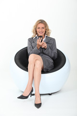 Businesswoman with cellphone sitting in funky chair