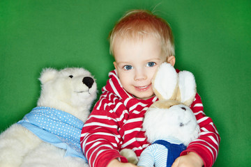 Glückliches Kleinkind mit Kuscheltieren
