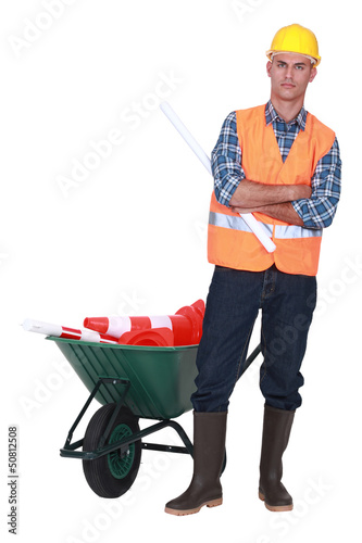 Angry tradesman standing in front of a wheelbarrow