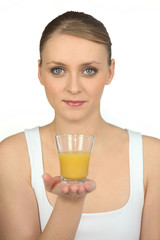 blonde woman showing a glass of orange juice