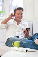 Mann hört Musik auf der Couch