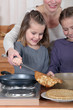Mother making pancakes with her two daughters