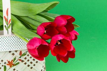 rote Tulpen auf Korb vor grünem Hintergrund