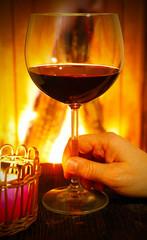 Glas Rotwein am Kamin trinken