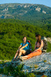 Two trekkers took a rest at the stone in Crimea mountains