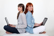 Two young women with laptops
