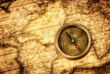 Fototapety Vintage compass lies on an ancient world map.