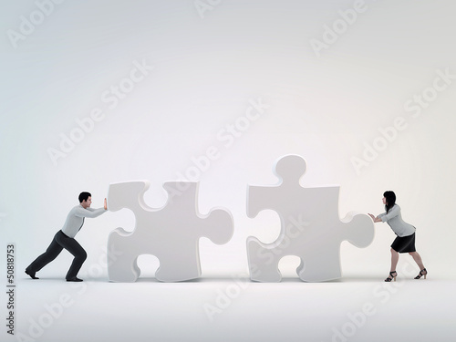 Teamwork, Man and woman pushing each other toward the puzzle.