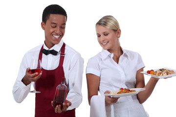 a wine waiter showing a bottle to a waitress