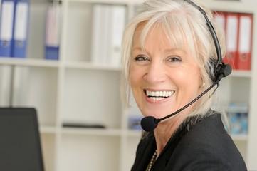 Attraktive Seniorin mit Headset