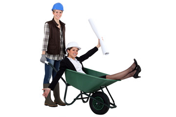 Woman pushing another woman in wheelbarrow
