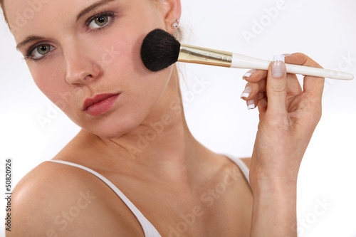 Woman applying blusher with brush