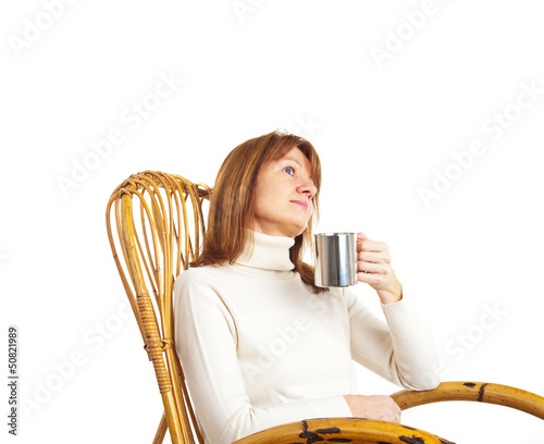 Beautiful woman enjoying a cup of coffee in a rocking chair