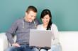 glückliches paar schaut lachend auf einen laptop