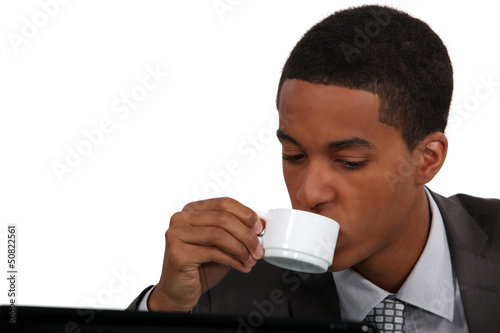 Businessman drinking coffee by laptop