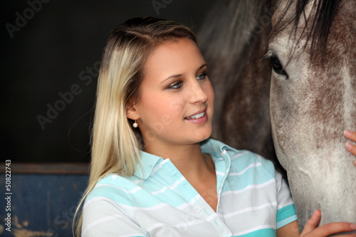 A young woman caressing a horse