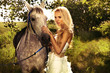 Beautiful blonde lady with posing with horse.