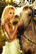 Portrait of gorgeous blonde girl with horse.
