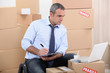 Man surrounded by cardboard boxes using a laptop