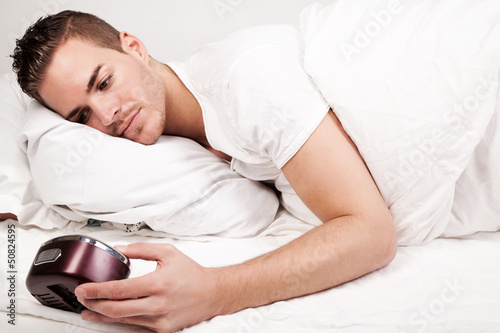 beautiful young man lying in bed looking at clock