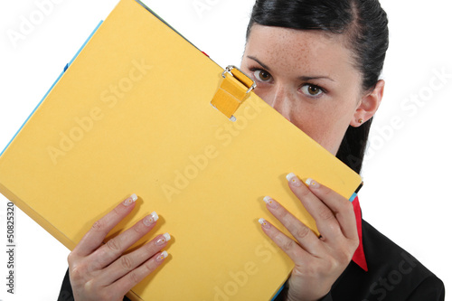Businesswoman covering face with file