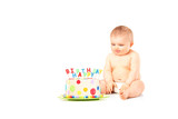 A 9 month old baby in diapers sitting next to a birthday cake