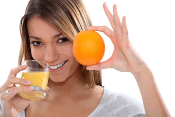 Woman holding up an orange and drinking orange juice