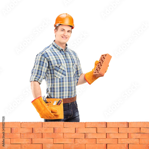 Male manual worker with helmet holding a brick behind a brick wa