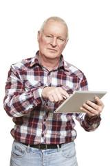 Senior man using tablet computer looking confused