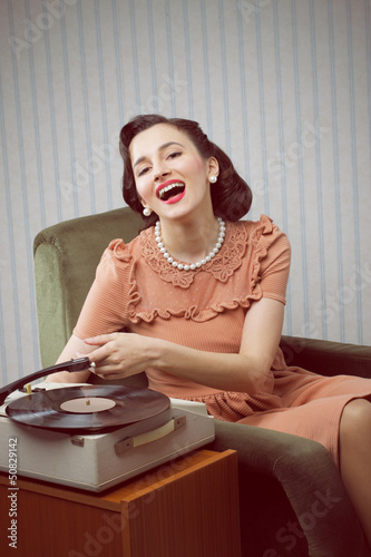 Young woman listening to music from a turntable