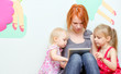 Mother and her daughters using tablet pc